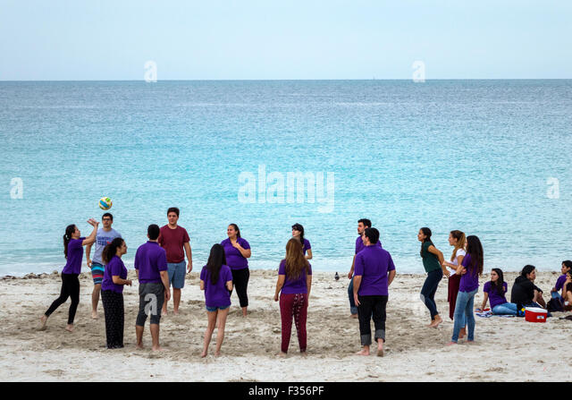 Miami Beach Florida sand Atlantic Ocean student teen Honor Society field trip playing game volleyball - Stock Image