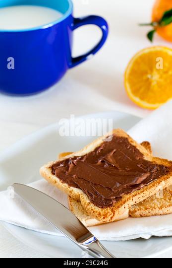 Breakfast with Chocolate Spread on Toast, Milk and Orange - Stock Image