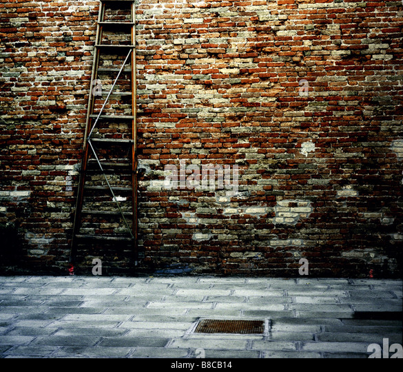 Exterior Wall Ladders : Ladder leaning against exterior wall stock photos
