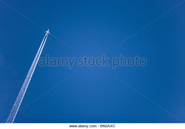 Airplane with contrail flying in clear, blue sky - Stock Image