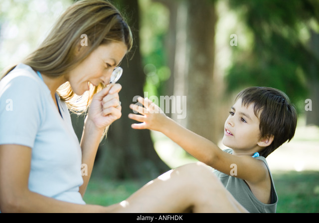 Mother and son, woman looking through magnifying glass while boy reaches for it - Stock Image
