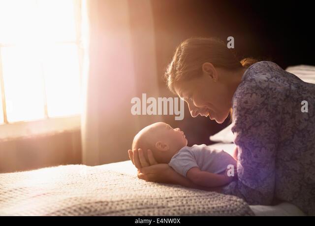 Mother holding baby boy (2-5 months) in bedroom - Stock-Bilder