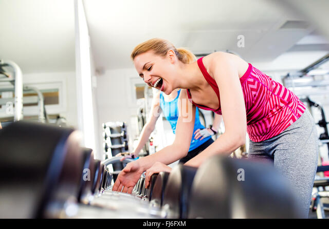 Detail of women in gym laughing, row of weights - Stock Image