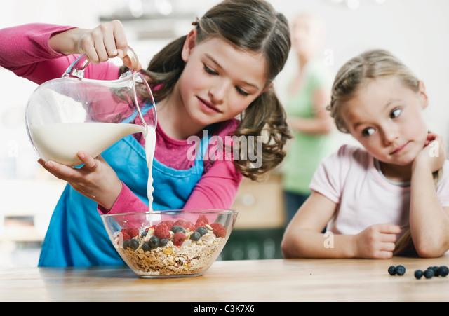 Germany, Cologne, Children preparing breakfast in kitchen - Stock-Bilder