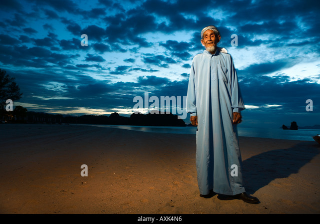 old elderly man on beach bank water ocean in cloth sky clouds scattered blue brown white sunset sunrise evening - Stock Image