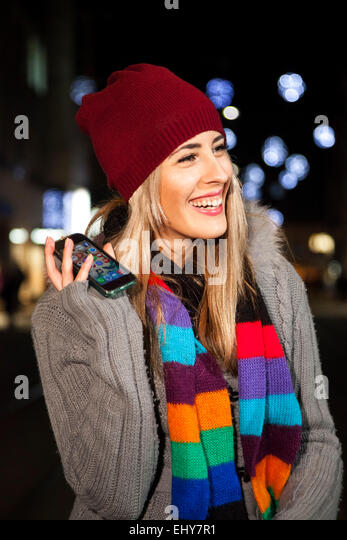 Portrait of young woman holding smart phone - Stock Image