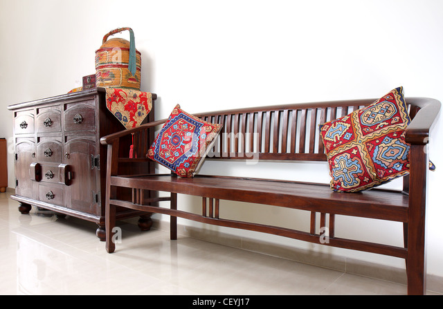 A teakwood Balinese-style bench next to a teakwood console table. - Stock-Bilder