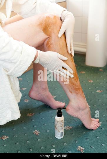 woman applying fake tan on her legs - Stock Image