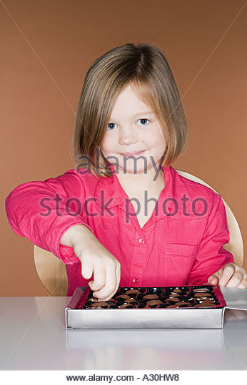 Girl taking a chocolate from the box - Stock Image