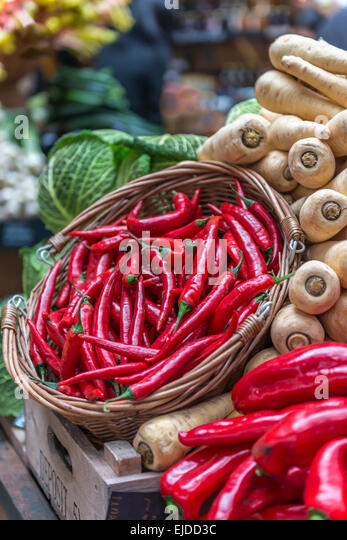 A basket of red chillies displayed on a vegetable stall against a backdrop of parsnips and cabbage - Stock Image