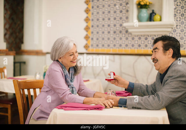 Older man proposing marriage to woman in restaurant - Stock Image