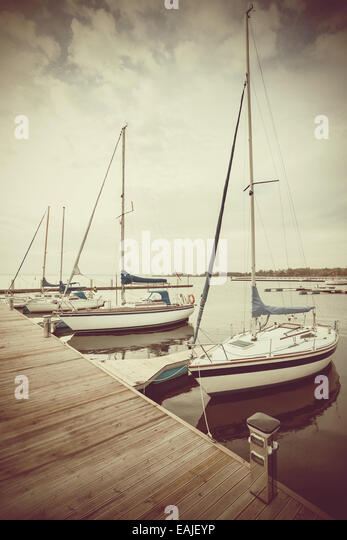 Retro filtered picture of yachts at pier. - Stock Image