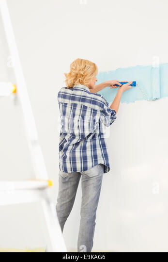 Rear view of woman painting wall with paint roller - Stock Image
