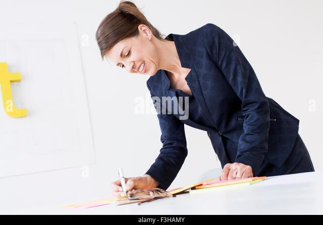 Mature woman wearing business attire writing on paperwork, looking down smiling - Stock Image
