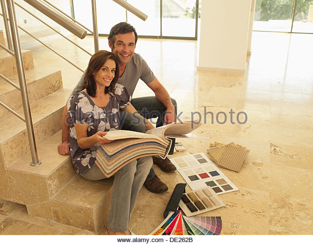 Couple looking at carpet samples in empty house - Stock Image