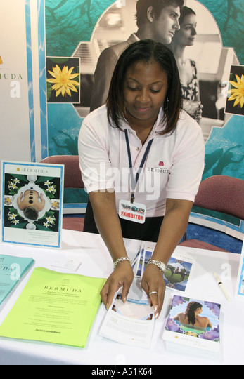 Florida Coconut Grove Convention Center Miami Herald Travel Expo Black female Bermuda tour promoter organizing - Stock Image