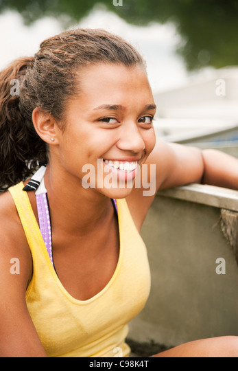 Teenage girl rowing boat on lake - Stock Image