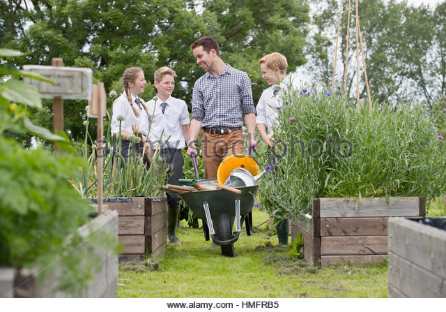 Teacher and middle school students with wheelbarrow learning gardening in vegetable garden - Stock-Bilder