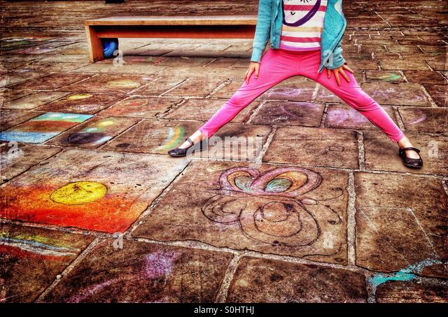 Young girl standing on pavement covered in chalk drawings - Stock-Bilder