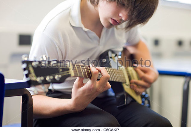 Close up of serious boy playing guitar - Stock-Bilder