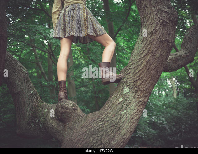 A young woman wearing a skirt is standing in a tree in the forest - Stock Image
