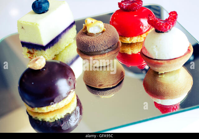 Small tasty desserts with different kind of cream flavoring - Stock Image