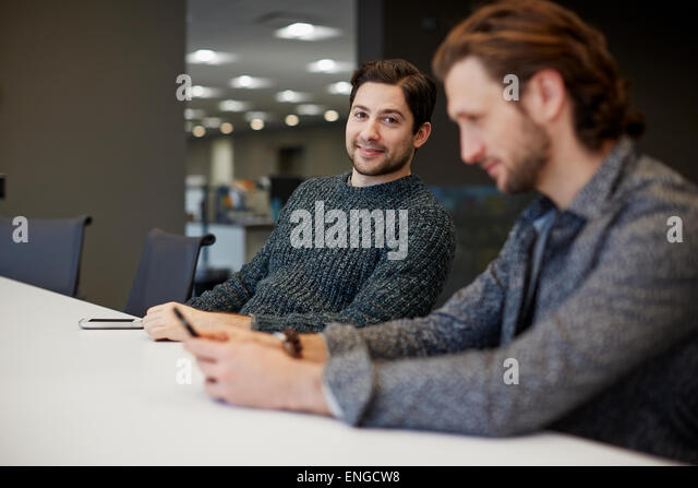 Two men seated at a table, one using his smart phone. - Stock Image