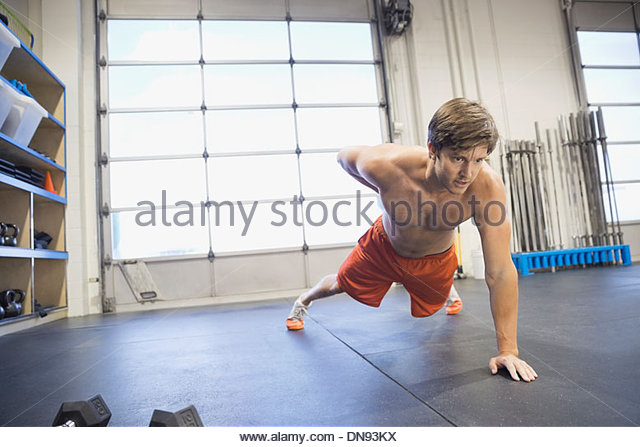 Man doing one arm push-ups in gym - Stock Image