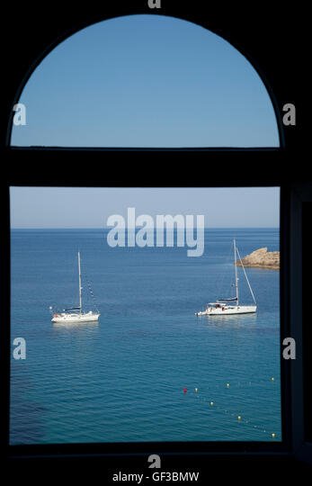 Sailboats anchored in the bay at Saint Elm, Mallorca, Spain are seen framed in window. - Stock Image