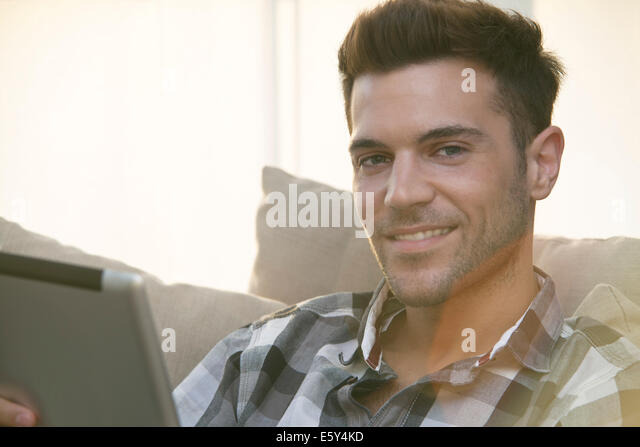 Young man using digital tablet at home - Stock Image