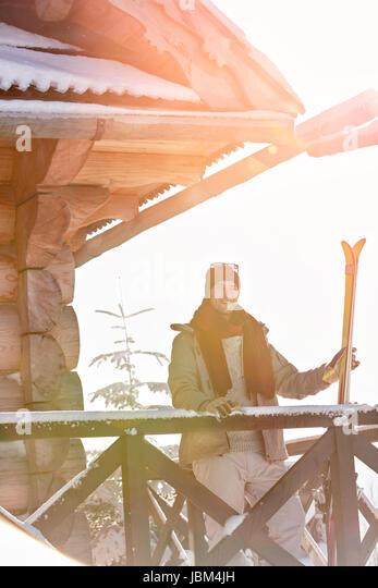 Portrait smiling male skier with skis on sunny cabin balcony - Stock-Bilder