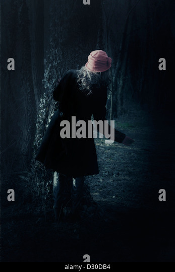 a woman with a black coat is standing behind a tree - Stock Image