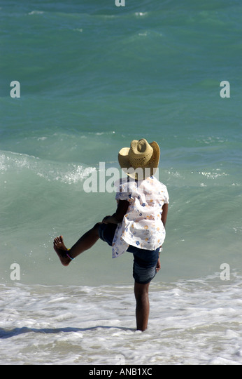 Bahamas Bahamian girl in straw hat dancing in surf - Stock Image