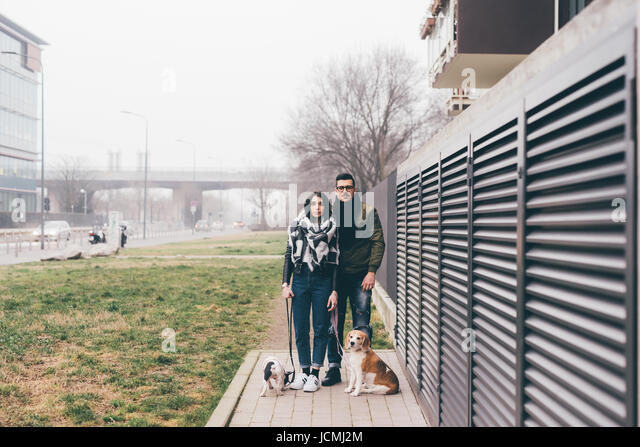 Young couple posing outdoor with dogs on a leash smiling - friendship, everyday life, happiness concept - Stock-Bilder