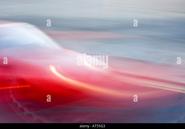 fast moving car, blurred camera pan, slow shutter speed camera technique, red - Stock Image