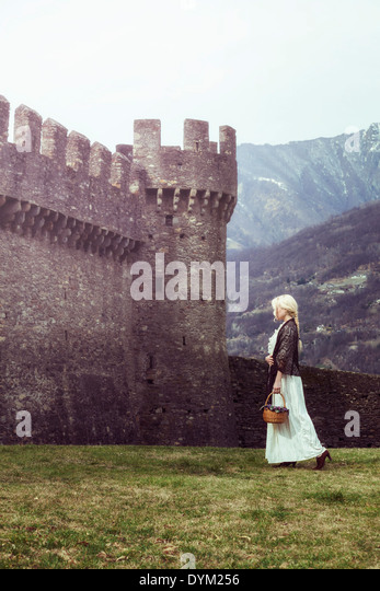 a woman in a white period dress is walking along a castle - Stock Image