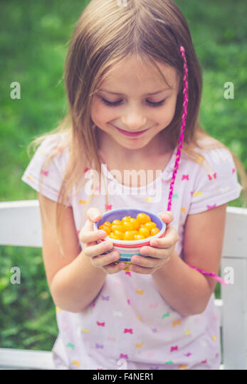 Girl with tomberries in bowl, yellow mini tomatoes - Stock Image