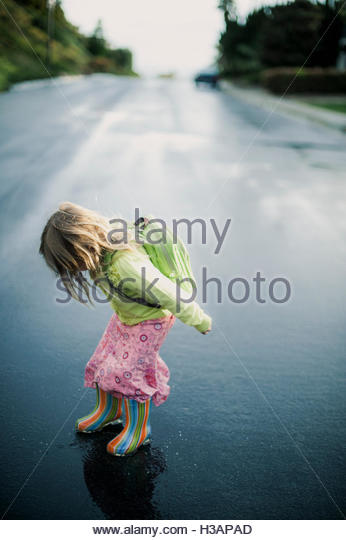 little girl coming home from school on a rainy day - Stock Image