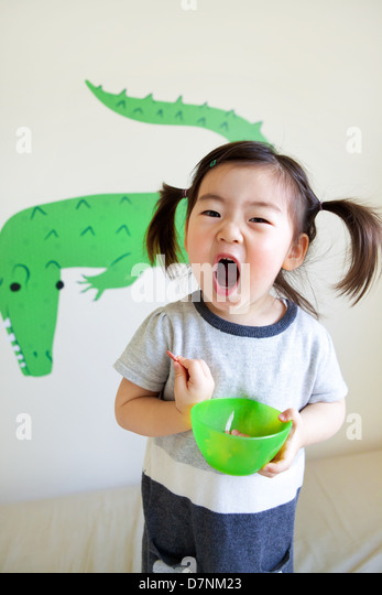 Korean American toddler in pigtails shouting to camera eating snacks from green bowl and crocodile wall art behind. - Stock-Bilder