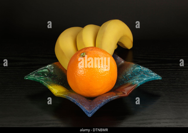 Bananas and orange in colored glass bowl - Stock Image