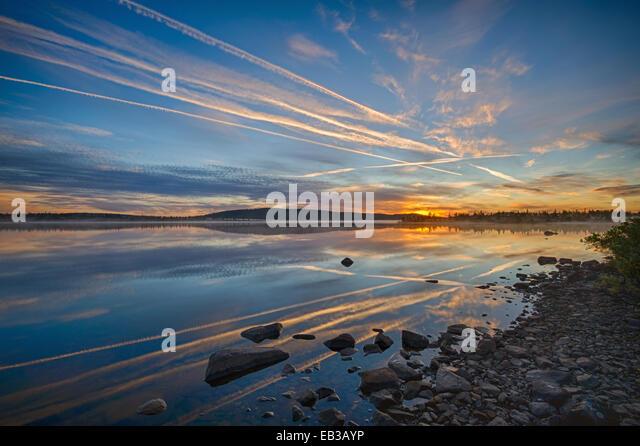 Vapor trails on sky at sunset - Stock Image