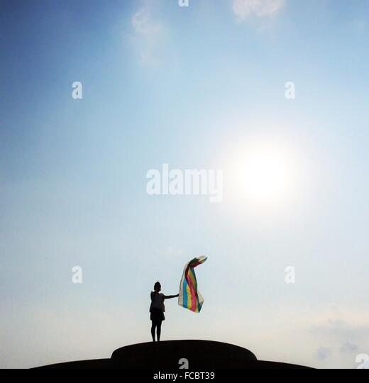 Low Angle View Of Silhouette Woman With Colorful Cloth Against Sky - Stock Image