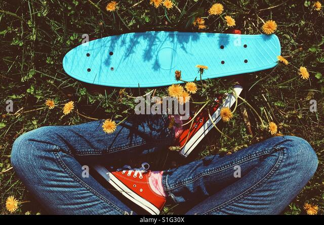 Penny board and woman's legs in red sneakers on the grass with yellow flowers - Stock-Bilder