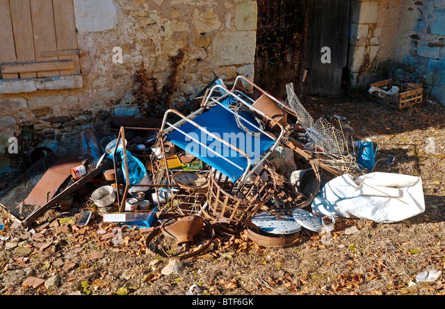 Household rubbish in front of abandoned cottage - France. - Stock Image