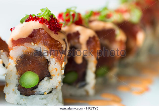 A dish of sushi, seaweed rolls and fish. - Stock Image