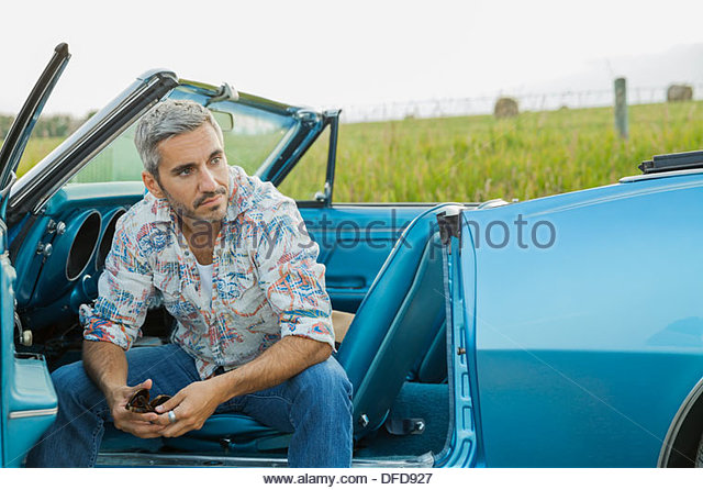 Mid adult man sitting in convertible - Stock Image