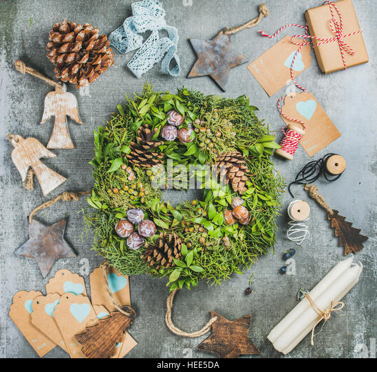 Christmas green wreath, pine cones, wooden toys, candles, decorative materials - Stock Image