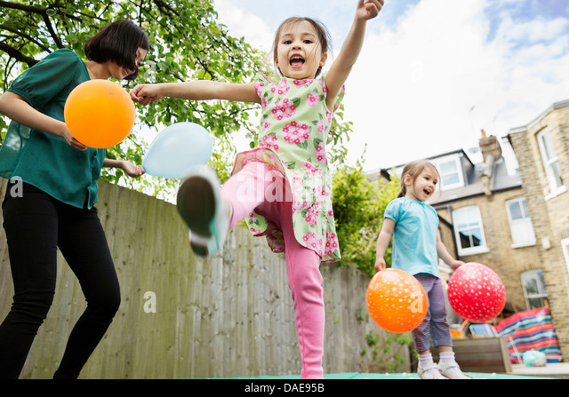 Mother and daughters playing in garden with balloons - Stock-Bilder