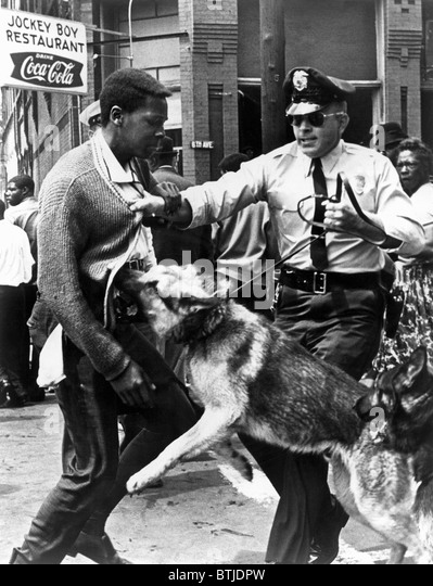 A Black man is attacked by a policeman and dog, 1963. - Stock Image