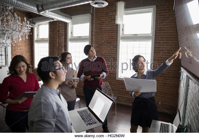 Hispanic designers meeting at television monitor in conference room - Stock Image